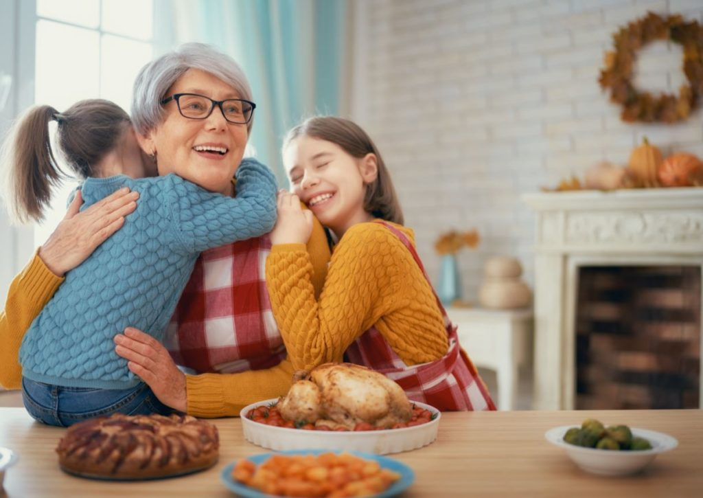 Woman hugging grandchildren at Thanksgiving dinner