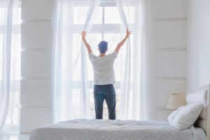 young man opening curtains in the morning